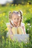 Kleines blondes Mädchen mit digitaler Tablette auf dem gelben Gebiet Lizenzfreies Stockbild