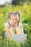 Kleines blondes Mädchen mit digitaler Tablette auf dem gelben Gebiet Stockfotografie