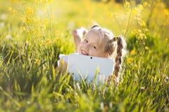 Kleines blondes Mädchen mit digitaler Tablette auf der Natur Lizenzfreie Stockbilder