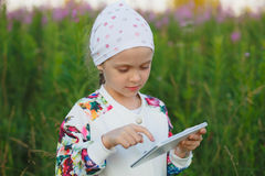 Kleines blondes Mädchen mit digitaler Tablette auf der Natur Stockfoto
