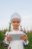 Kleines blondes Mädchen mit digitaler Tablette auf der Natur Stockbilder