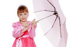 Kleines blondes Mädchen mit einem rosa Regenschirm Lizenzfreie Stockbilder