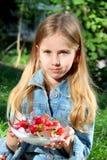 Kleines blondes Mädchen mit einer Platte von frischen Erdbeeren in der Sommerzeit Lizenzfreie Stockfotografie