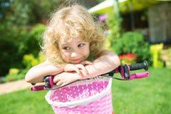 Kleines blondes Mädchen mit Fahrrad Stockbild