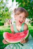 Kleines blondes Mädchen mit großer Scheibenwassermelone Stockfotografie