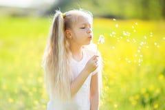 Kleines blondes Mädchen mit Löwenzahnblume Stockbild