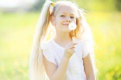Kleines blondes Mädchen mit Löwenzahnblume Lizenzfreie Stockbilder
