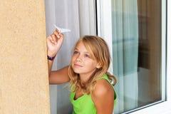 Kleines blondes Mädchen mit Papierfläche im Fenster Lizenzfreie Stockbilder