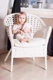 Kleines blondes Mädchen mit weichem Spielzeug sitzt auf großem geflochtenem Stuhl Lizenzfreies Stockbild