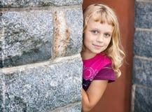 Kleines blondes Mädchen schaut heraus von hinten die Wand Stockfotos