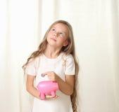 Kleines blondes Mädchen setzt Münze in piggy moneybox Lizenzfreies Stockfoto