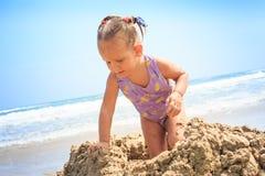 Kleines blondes Mädchen springt auf Sand-Haufen auf Strand herum Lizenzfreie Stockbilder