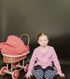 Kleines blondes Mädchen und Puppen Pram auf schwarzem Hintergrund Kleines Mädchen sitzt auf schwarzem Hintergrund Lizenzfreies Stockbild