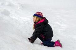 Kleines blondes Mädchen, das im Schnee spielt Stockfotos