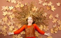 Kleines blondes Mädchen des Herbstfalles auf getrocknetem Baum verlässt Lizenzfreie Stockfotos