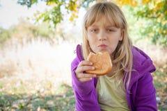 Kleines blondes Mädchen im Park isst kleine Torte Stockbilder