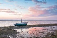 Kleines Boot auf dem See bei Sonnenuntergang, Dämmerung Stockfotos