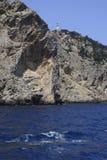 Kleines Boot, blauer Ozean und felsige Küste Stockbilder