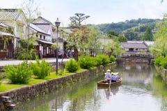 Kleines Boot, das auf Kanal in Kurashiki, Japan geht stockbild
