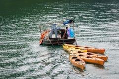 Kleines Boot, das bunte Kajaks schleppt Stockbild