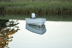Kleines Boot, das festgemacht wird und in einem See am frühen Abend reflektiert ist Stockfoto