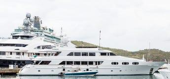 Kleines Boot durch enorme Yacht durch Kreuzschiff Stockbild