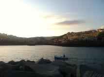 Kleines Boot in einer Bucht vor einer kleinen italiant Stadt Lizenzfreie Stockbilder