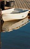 Kleines Boot gebunden an einem hölzernen Dock und an einer Reflexion Lizenzfreie Stockbilder