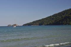 Kleines Boot heraus auf dem Meer mit blauem klarem Wasser und blauem Himmel Stockfotografie