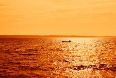 Kleines Boot im Meer mit orange Himmel und Wasser Stockfotografie