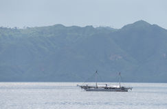 Kleines Boot im ruhigen Wasser auf einem Hintergrund von großen Hügeln Singapur Stockbild