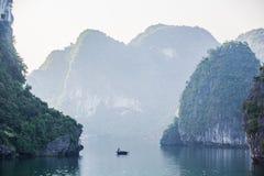 Kleines Boot mit dem Hintergrund von Halong-Bucht Stockfotos