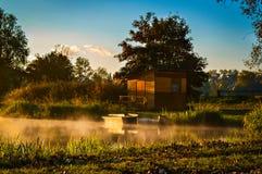 Kleines Boot verankert nahe dem Häuschen während des Sonnenaufgangs Lizenzfreies Stockbild