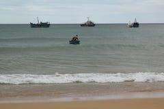 Kleines Boot versucht, zum großen Boot auf dem Meer bei Phu Yen, Vietnam - September 5,2018 zu gehen lizenzfreies stockbild