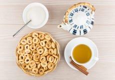 Kleines Brot schellt im Korb, Tee, Zimtstangen, Teekanne Stockbilder
