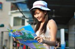 Kleines chinesisches asiatisches touristisches Mädchen, das ihre Karte 2 verwendet Lizenzfreie Stockfotografie