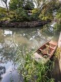 Kleines chinesisches hölzernes Boot mit reflektierten Bäumen im bescheidenen Adm Stockbilder