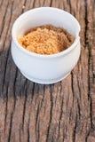 Kleines Cup brauner Zucker auf hölzernem Teakholz lizenzfreies stockbild