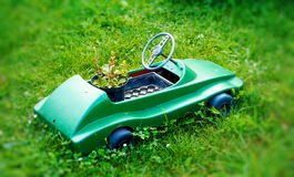 Kleines dekoratives Plastikfahrzeug mit Blumentopf auf grünem Rasen Lizenzfreies Stockbild