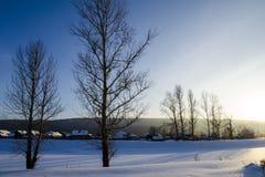 Kleines Dorf im Wintersonnenuntergang Stockbild