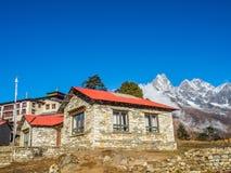 Kleines Dorf mit dem schönen Schnee bedeckte Gebirgshintergrund mit einer Kappe Lizenzfreie Stockfotografie