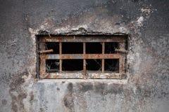 Kleines dunkles Kellerfenster Stockfotografie