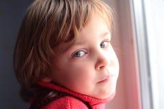 Kleines durchdachtes Mädchen am Fenster Stockfotografie