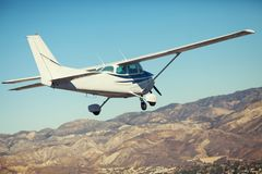 Kleines einmotoriges Flugzeugfliegen im herrlichen Sonnenunterganghimmel durch das Wolkenmeer ?ber den gro?artigen Bergen lizenzfreie stockfotografie