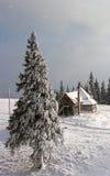 Kleines einsames Haus auf einem schneebedeckten Hügel Stockfotografie