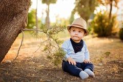 Kleines entzückendes Baby in einem Strohhut und in blauen Hosen, die w sitzen Stockbild