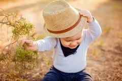 Kleines entzückendes Baby in einem Strohhut und in einem blauen Hemd, die n sitzen Lizenzfreies Stockbild