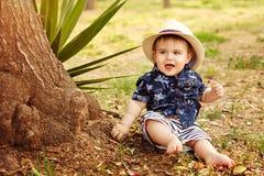 Kleines entzückendes Baby in einem Strohhut und in einem blauen Hemd, die s sitzen Lizenzfreies Stockbild