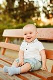 Kleines entzückendes Baby mit großen braunen Augen in den Denimkurzen hosen und Lizenzfreies Stockfoto