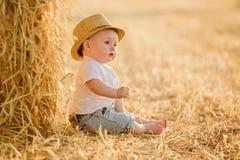 Kleines entzückendes Baby mit großen braunen Augen in einem Hut sitzt in a Lizenzfreie Stockbilder